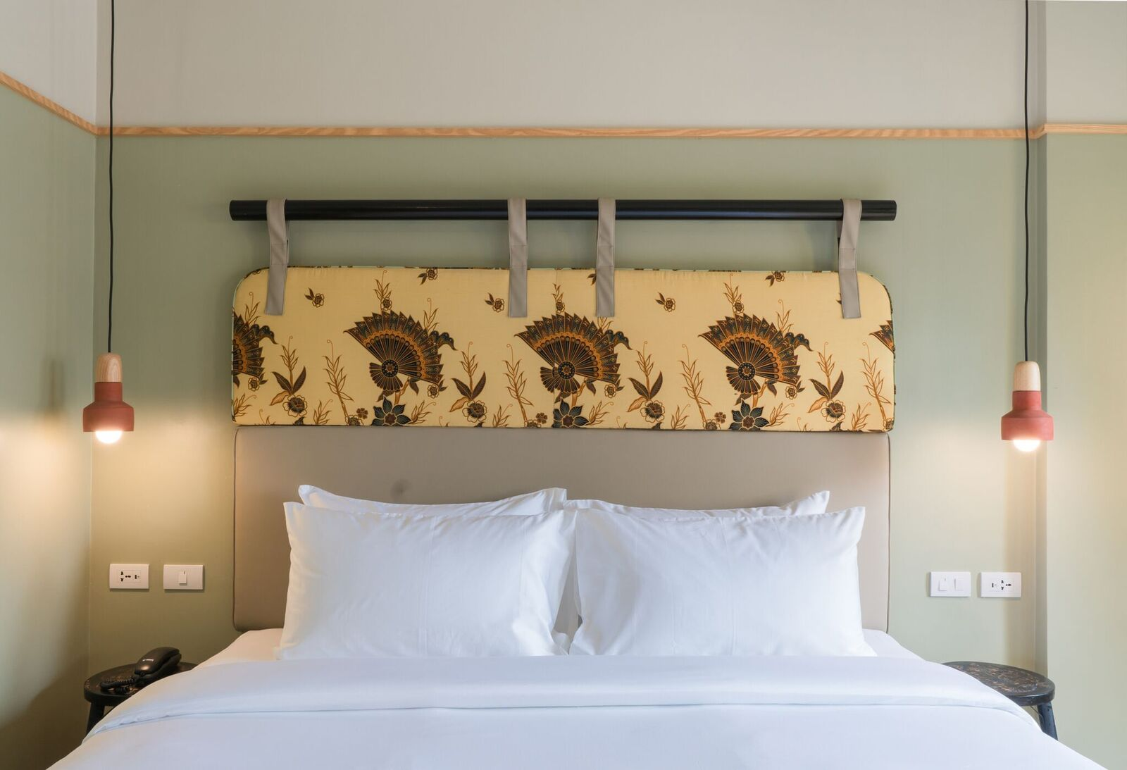 Bed and custom fabric headboard in guestroom at Blanket Hotel Phuket Town